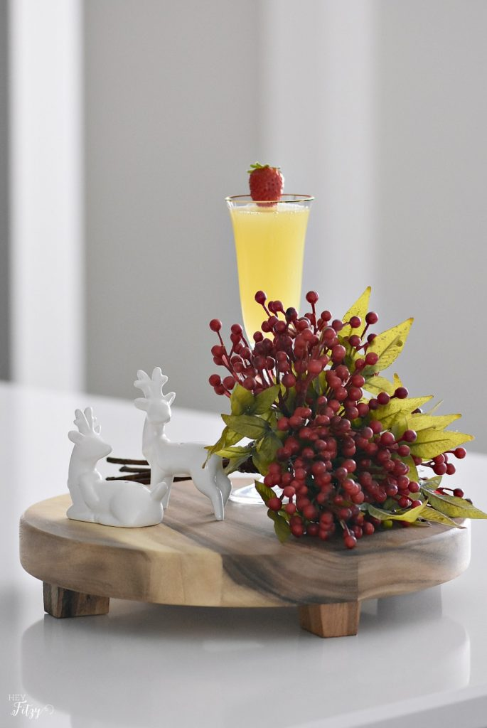 Mimosas on a wood board with berries and reindeer
