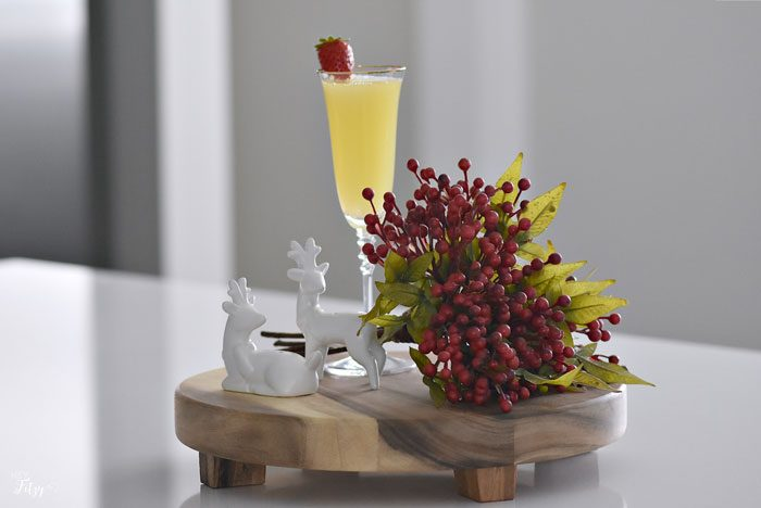 cocktail in a champagne flute sitting alongside a berry sprig and ceramic reindeer