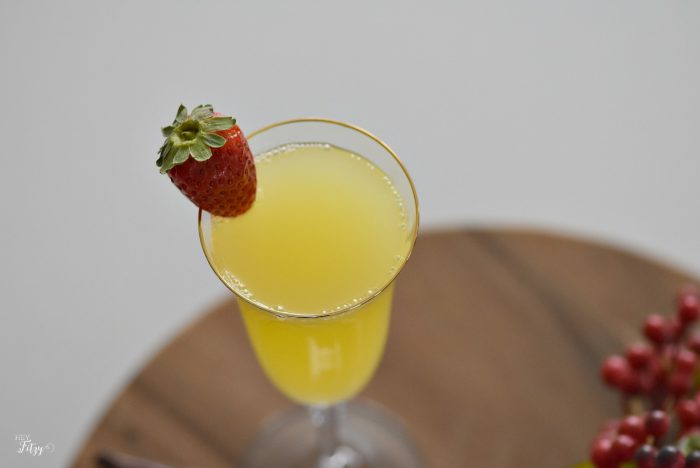 close up of cocktail in a champagne flute garnished with a single strawberry