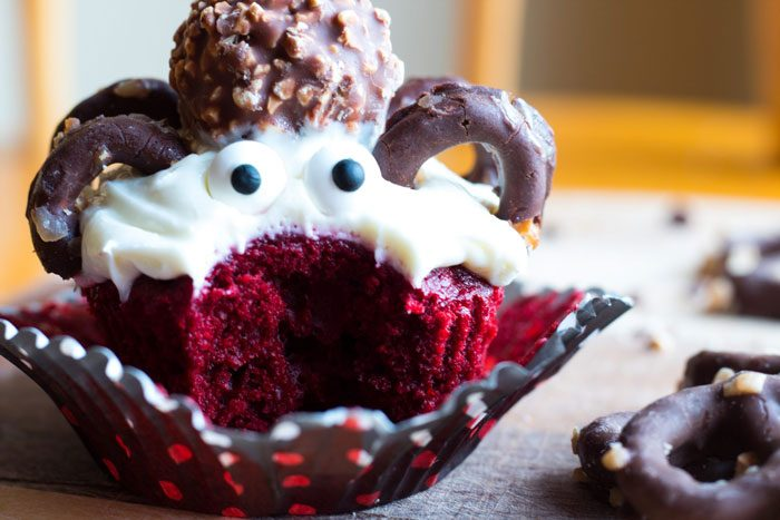 A cute cupcake decorated to look like a spider with pretzels, candy eyes, and a truffle.