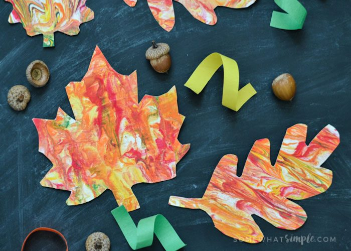 A picture of paper painted with shaving cream marbled effect and cut into fall leaf shapes