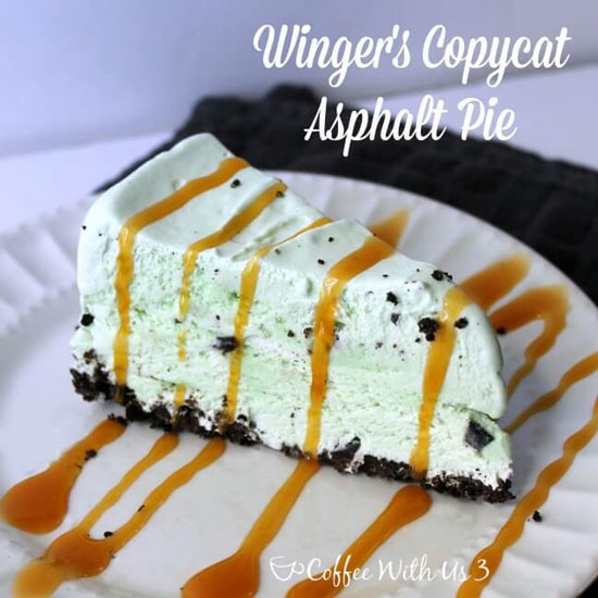 A slice of mint chocolate chip cake with an oreo cookie crust and a drizzle of caramel on top.