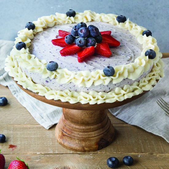 A blueberry ice cream cake with fresh berries, and piped frosting around the edges on a wooden pedestal cake stand.