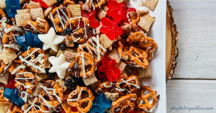 A plate of snack mix with chocolate drizzled pretzels, chex cereal, dried blueberries and gummy stars
