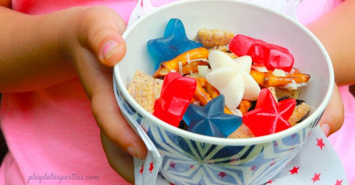 A child holding a bowl of patriotic snack mix