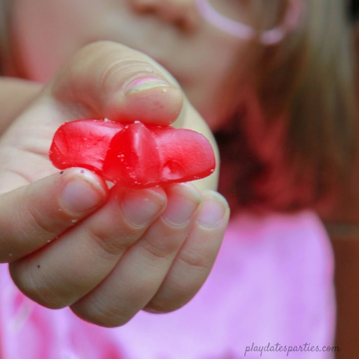 A picture of a child holding out a red gummy star