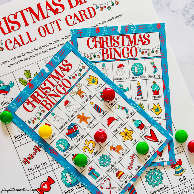 Call out page and two Christmas bingo cards on a marble counter with colorful candies as markers