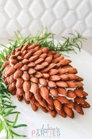 Cheese ball in the shape of a pine cone covered in almonds with sprigs of rosemary garnishing the top