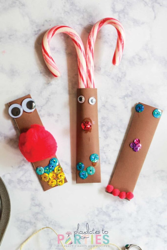 three brown pockets with faces made out of pom poms, sequins, and jingle bells. One pocket is made into a reindeer with candy canes as antlers