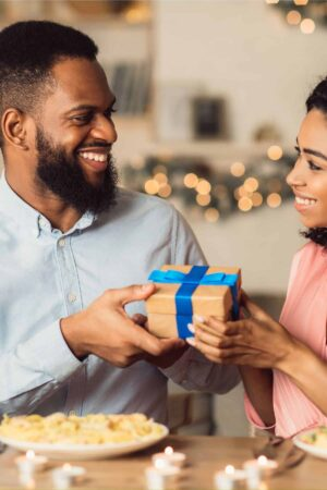happy couple exchanging gifts at a table
