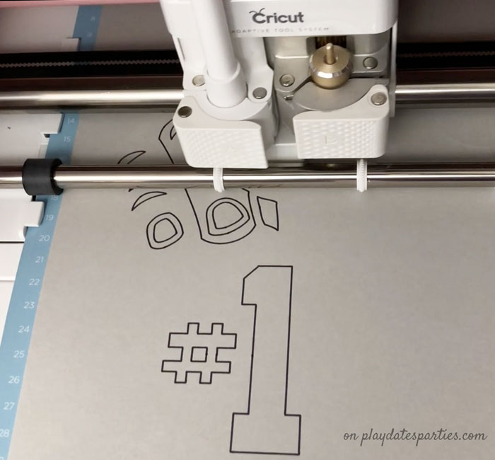 A picture of a Cricut Maker drawing the design for the fan finger football craft