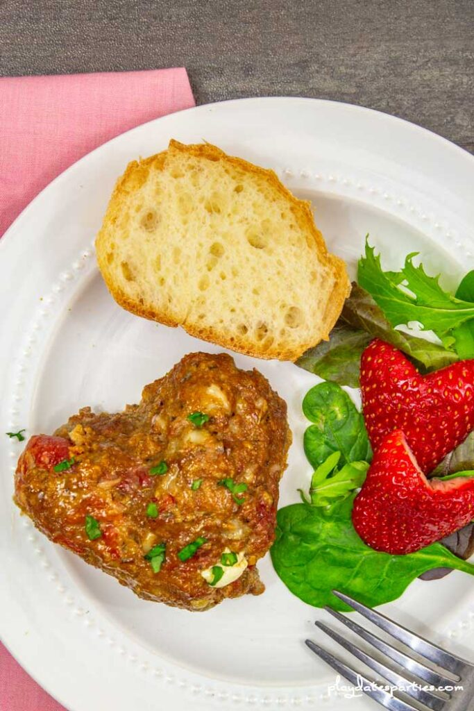heart shaped meatloaf on a plate with heart shaped strawberries and salad