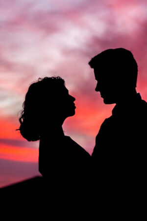 Silhouette of a couple looking at each other in front of a sunset