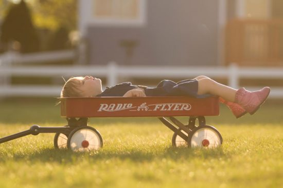 child laying in a red wagon on a sunny day