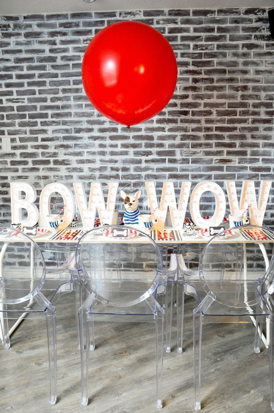 "A dining table set up for a bulldog themed party with the words ""Bow Wow"" spelled in large marquee letters and a single red balloon floating above"