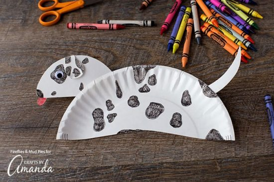 paper plate that looks like a puppy with black spots on a brown table next to crayons and scissors