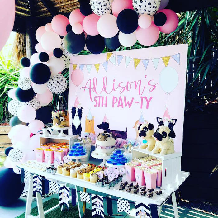 "a puppy themed birthday party set up in pink and black with a backdrop that says ""Addison's 5th paw-ty"" and an asymmetrical pink, black and white balloon garland"