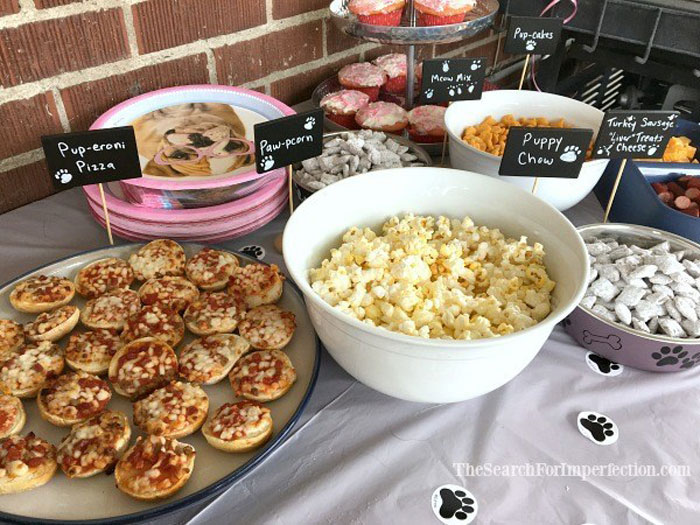 A buffet table full of puppy themed party food with labels