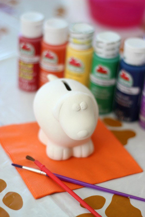 a small unpainted ceramic dog surrounded by paints and paintbrushes