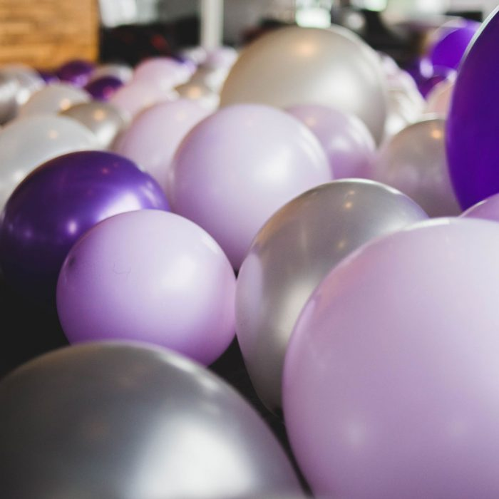 Hundreds of balloons without helium filling the floor of a room