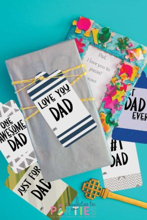 father's day gift tags scattered around gifts on a blue surface
