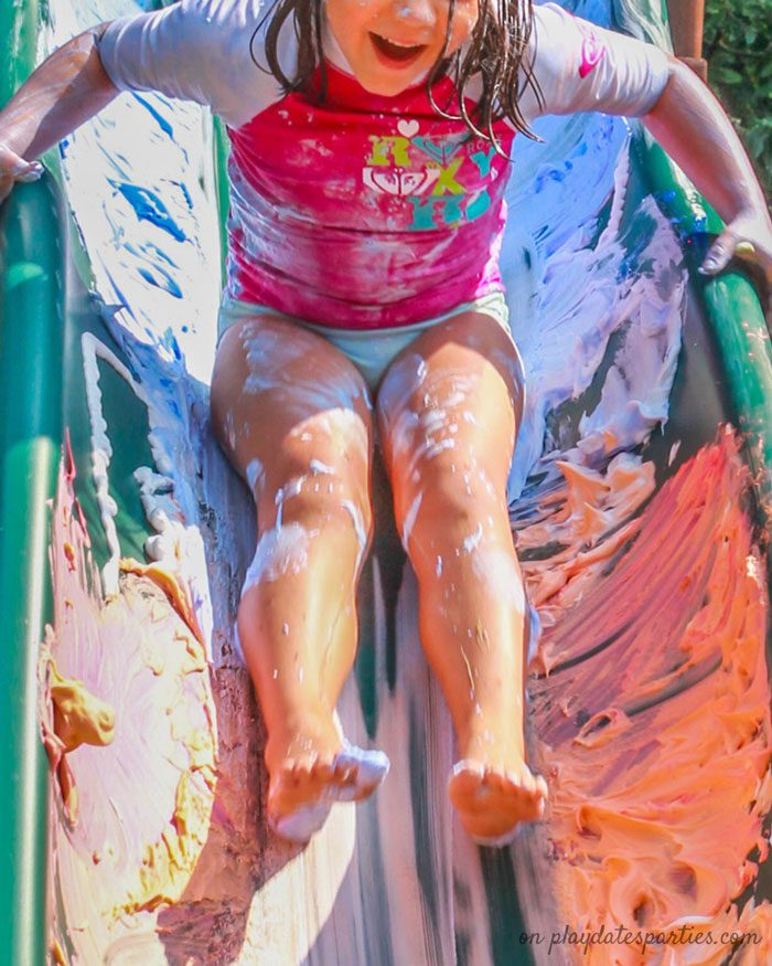 Photo of a child on a slide with colorful shaving cream