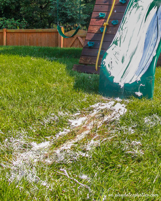 Photo of a slide covered with shaving cream and the shaving cream skid marks in the grass