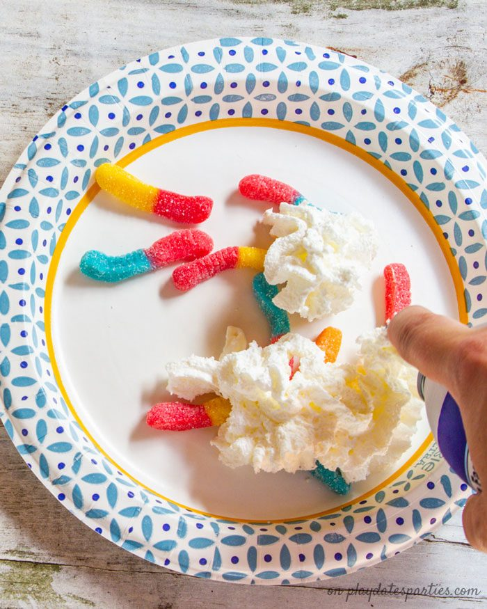 Covering gummy worms with whipped cream for a fun party game