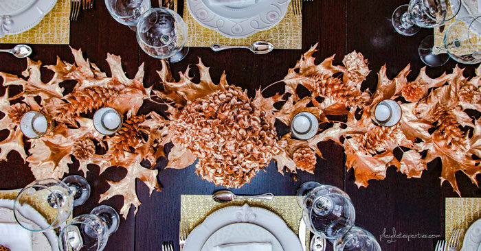 Overhead view of gold Thanksgiving decor on a table with gold leaves, pine cones, placemats, and gold flowers