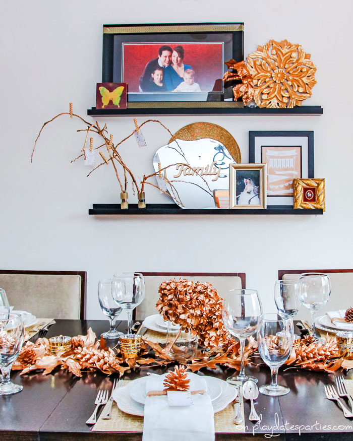 Gold Thanksgiving decor, including gold table decorations, gold branches, and gold sign that says family.