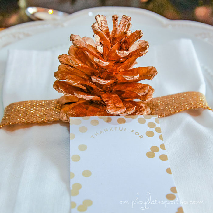 Close up of a napkin wrapped in gold ribbon with a gold pine cone and a card that says Thankful for
