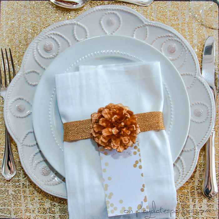 Overhead view of gold Thanksgiving table setting with a gold placemat, gold wrapped napkin, and gold pine cone