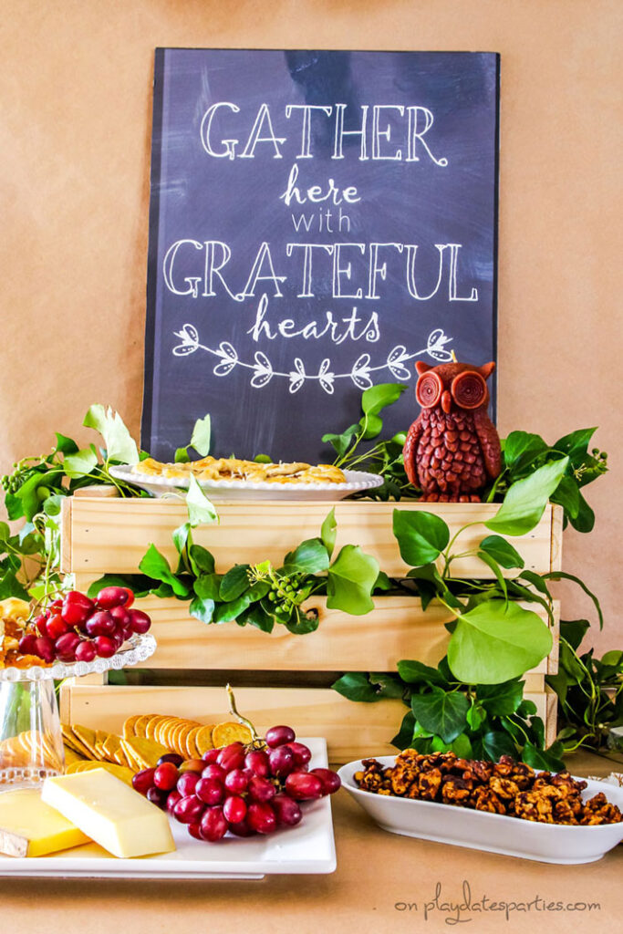 Inexpensive Thanksgiving table decorations on a buffet: a printable sign, a wood crate, an owl candle, and fresh branches from the backyard