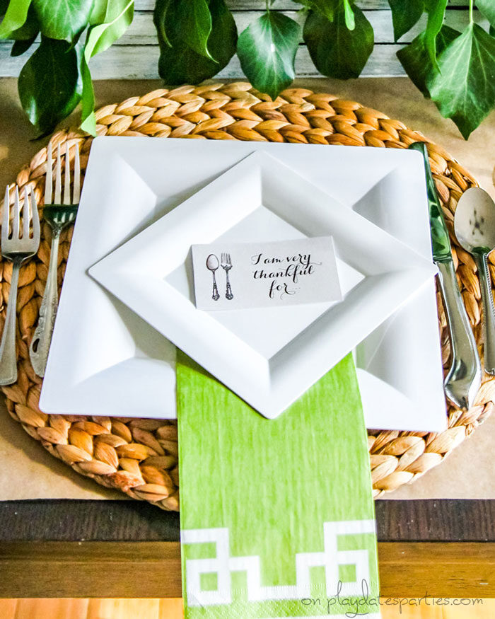 Inexpensive Thanksgiving table setting with disposable plates, woven placemats and a brown paper tablecloth