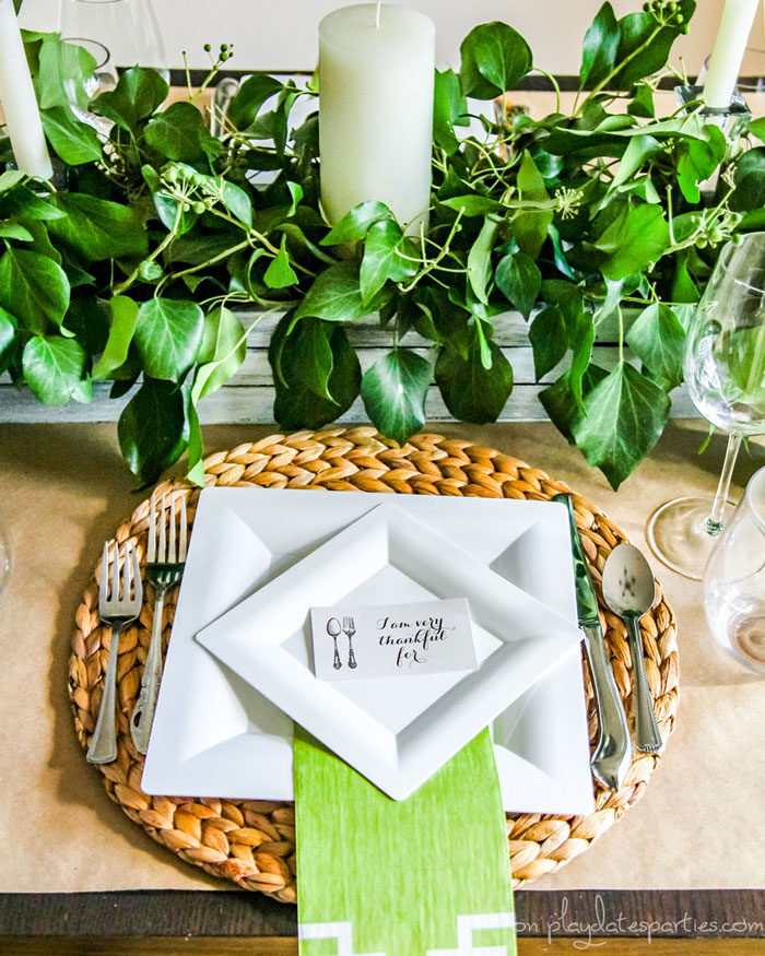 Thanksgiving table with a centerpiece that has a wood box filled with greenery, candles, woven placemats, white plates and a printable thankful card