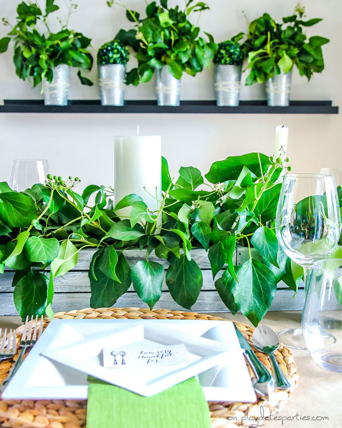 Fresh greenery on a Thanksgiving table and displayed in vases on the wall behind the table