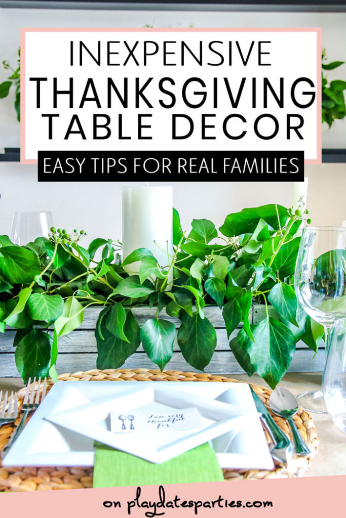 Thanksgiving table set with white plates greenery and candles with the text inexpensive Thanksgiving table decor. Easy tips for real families
