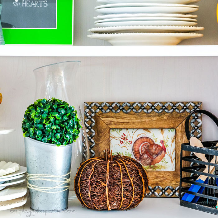 A kitchen hutch with inexpensive Thanksgiving decor: a napkin with a picture of a turkey that's been put inside a wood frame and a twig pumpkin