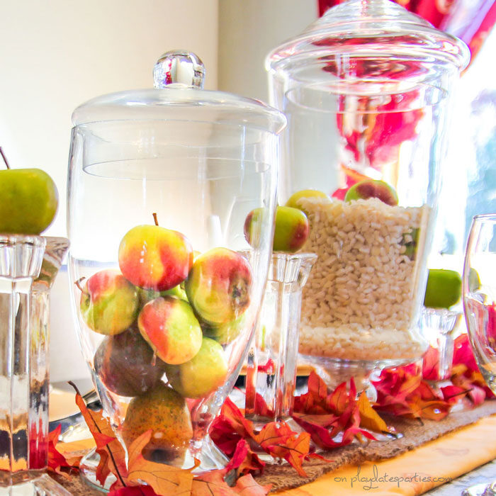 Close up of Thanksgiving centerpieces with hominy and fresh baby apples in apothecary jars