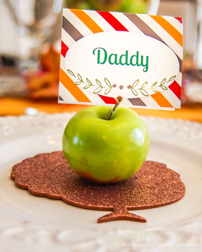 Vintage style Thanksgiving plates with a gold turkey cutout and a fresh apple as a place card holder