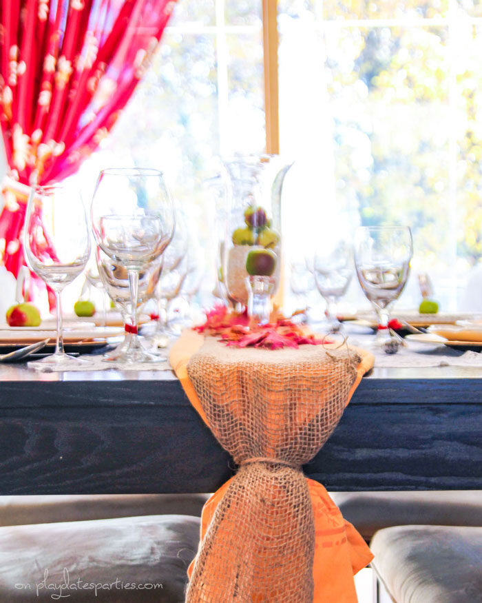 A gold tablecloth folded up as a table runner with a burlap ribbon and faux fall leaves on top for a vintage feel.