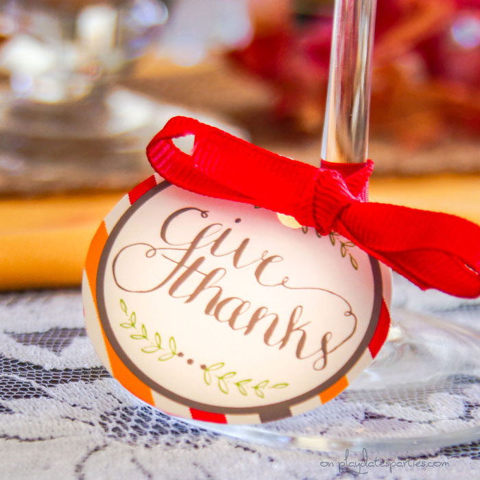 Thanksgiving printable tag on a wine glass stem that reads Give Thanks