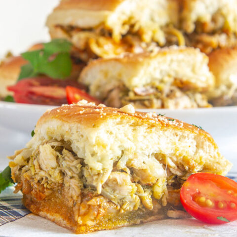 close up of chicken pesto sliders with a plate of sliders in the background