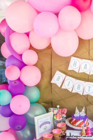 A pink, purple, and teal balloon garland draped over a party buffet.
