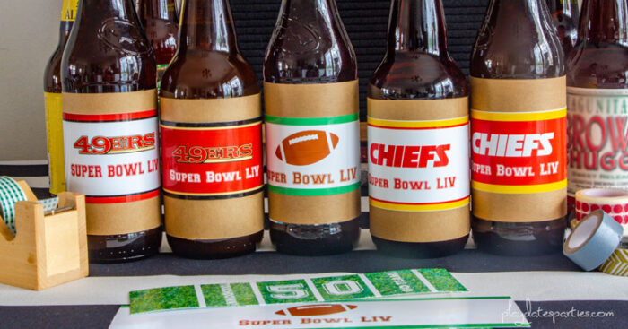 beer bottles in a row with super bowl printable labels on them and washi tape next to the bottles