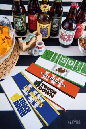 6 bottle label designs with a football motif on a black and white stripe table surrounded by beer bottles and chips