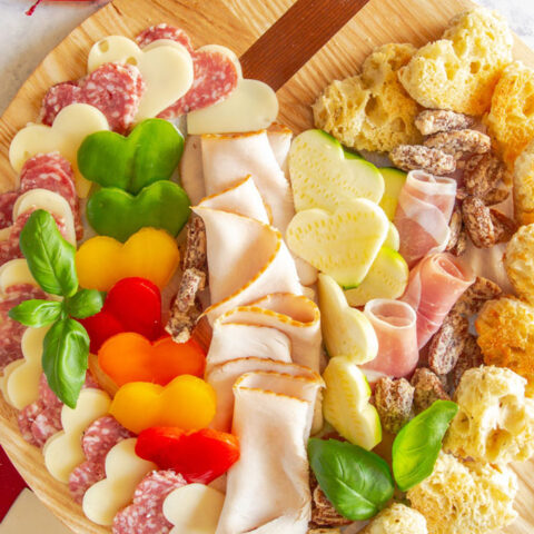 Valentine's Day charcuterie board with heart shaped vegetables, cheese, meat, and croutons
