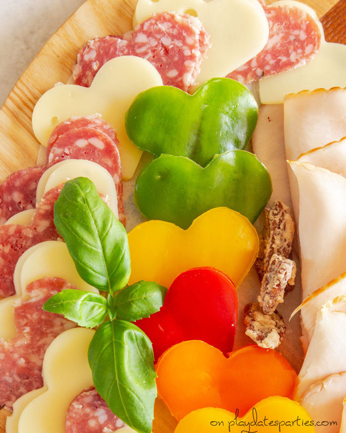 close up of heart shaped vegetables, swiss cheese, and salami
