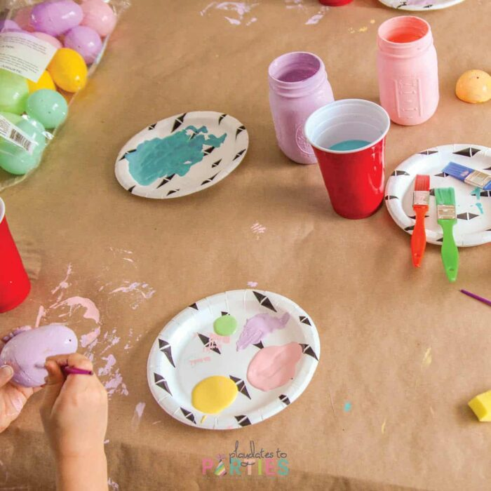 painting mason jars with kids, with the first coat painted, and a child's hands painting a plastic easter egg