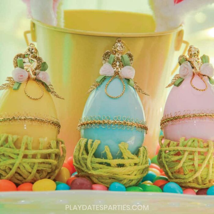 yellow pink and blue plastic eggs decorated Faberge style with gold trim, gold cherubs and fabric rosettes